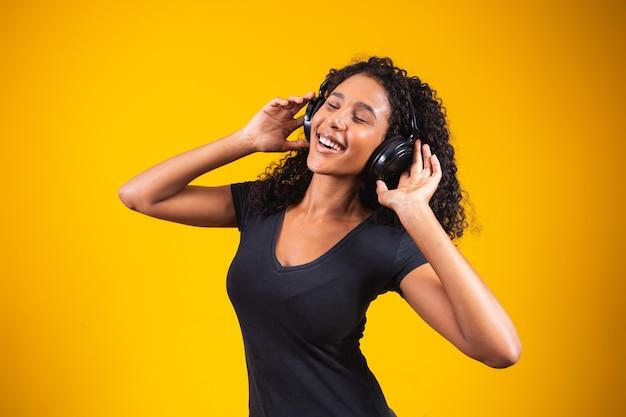 Jonge afrikaanse vrouw die een koptelefoon op gele achtergrond draagt