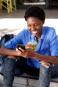 Jonge afrikaanse vrouw die een sap heeft en telefoon in openlucht met behulp van