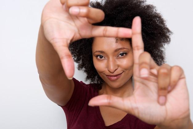 Jonge afrikaanse vrouw die frame met vingers maken tegen witte muur