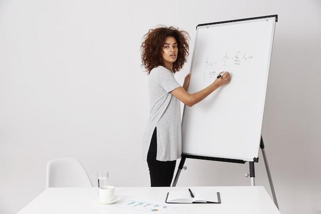 Jonge afrikaanse vrouw die haar ideeën uitleggen aan een investeerder of een bus zijn bij het bouwen van succesvol bedrijfsproces, startincubatoronderzoek, spoedig miljonair worden, wijzend op het concept.