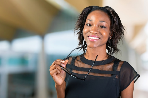Jonge afrikaanse vrouw die haar oogglazen en het glimlachen houdt