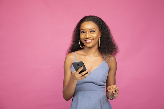 Jonge afrikaanse vrouw die online koopt met haar smartphone en een creditcard