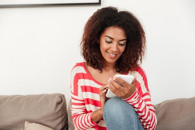 Jonge afrikaanse vrouw die op bank op smartphone babbelt
