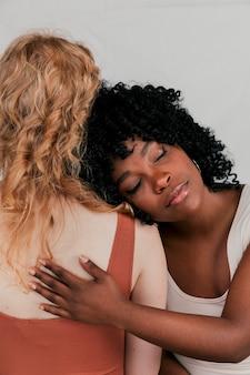 Jonge afrikaanse vrouw die op de schouder van het blonde wijfje leunt