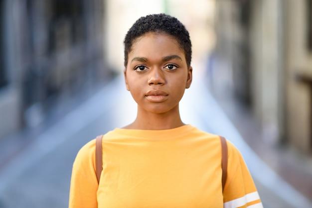 Jonge afrikaanse vrouw die vrijetijdskleding draagt die camera bekijkt.
