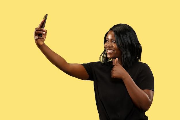 Jonge afrikaanse vrouw geïsoleerd op gele studio