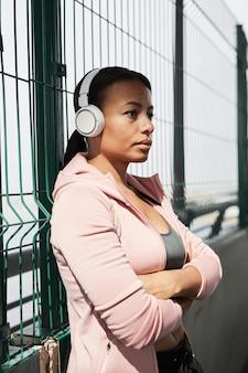 Jonge afrikaanse vrouw in draadloze koptelefoon die naar muziek luistert terwijl ze buiten staat