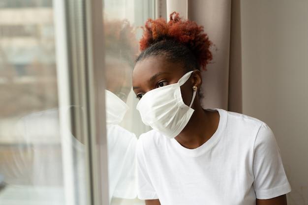 Jonge afrikaanse vrouw in medisch masker bij het raam