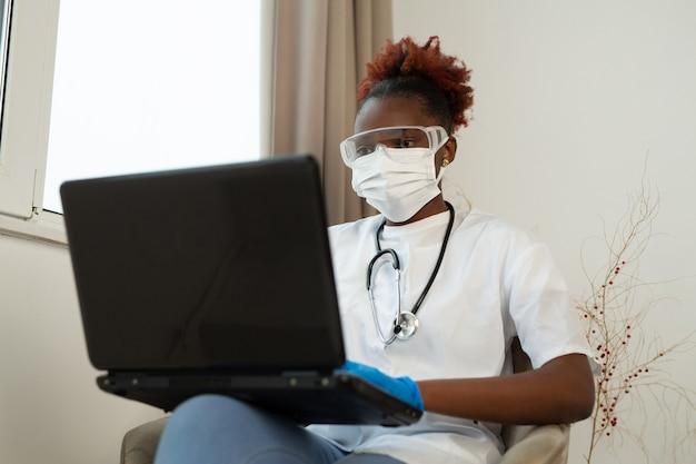 Jonge afrikaanse vrouw in medisch uniform met laptop