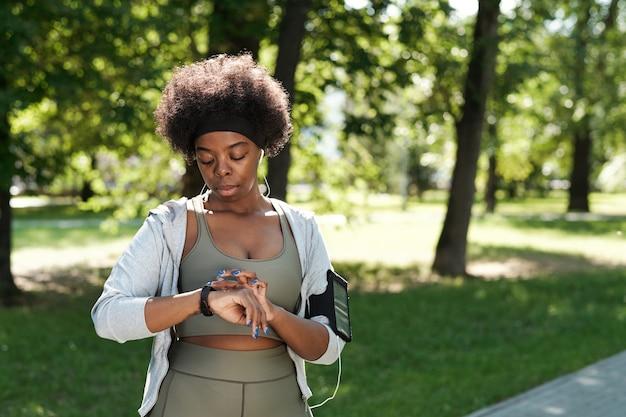 Jonge afrikaanse vrouw in sportkleding kijken naar smartwatch