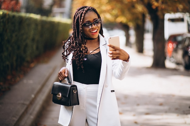 Jonge afrikaanse vrouw in wit pak met behulp van de telefoon