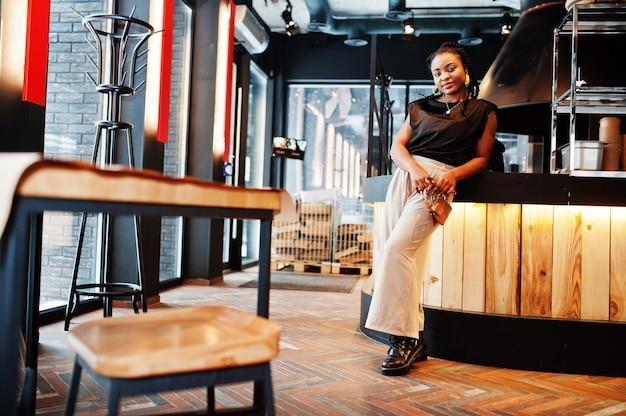 Jonge afrikaanse vrouw in zwarte blouse in café.