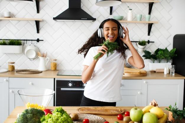 Jonge afrikaanse vrouw luistert jovially naar muziek via een koptelefoon en houdt dille