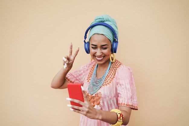 Jonge afrikaanse vrouw met behulp van mobiele telefoon-app voor het maken van afspeellijstmuziek