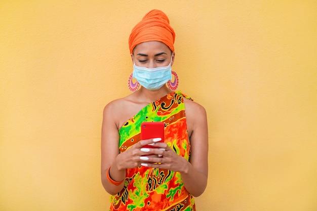 Jonge afrikaanse vrouw met behulp van mobiele telefoon terwijl het dragen van een beschermend gezichtsmasker tijdens de uitbraak van het coronavirus