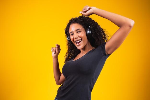 Jonge afrikaanse vrouw met koptelefoon die actief danst, geïsoleerd op gele muur, luisterend naar muziek die vrolijk lacht.