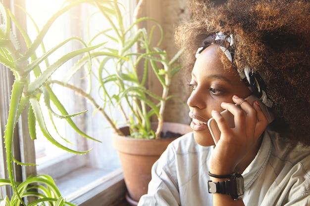 Jonge afrikaanse vrouw met krullend haar praten over de telefoon