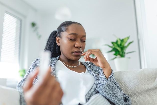 Jonge afrikaanse vrouw met zelftestend zelf toegediend wattenstaafje en medische buis voor coronavirus covid-19, voordat ze thuis zelf wordt getest