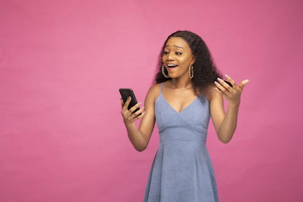 Jonge afrikaanse vrouw raakte opgewonden bij haar eerste online aankoop met haar smartphone