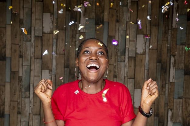 Jonge afrikaanse vrouw viert feest met rondzwevende confetti
