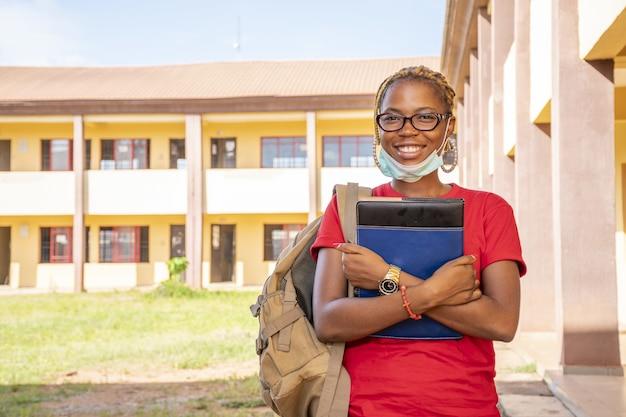 Jonge afrikaanse vrouwelijke student met een gezichtsmasker die haar schoolboeken bij een campusgebied houdt