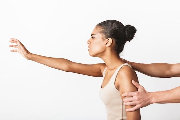 Jonge afrikaanse vrouwenzitting terwijl de hand van de man haar schouders houdt die op wit worden geïsoleerd