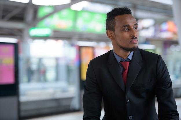 Jonge afrikaanse zakenman denken tijdens het wachten op de trein st