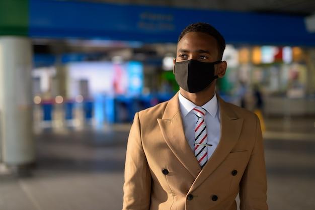 Jonge afrikaanse zakenman die met masker denkt voor bescherming tegen de uitbraak van coronavirus bij het skytrain-station