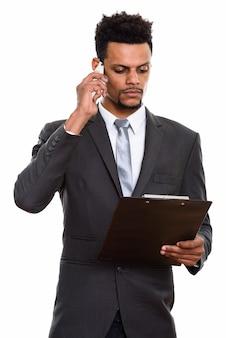 Jonge afrikaanse zakenman die op klembord leest terwijl het op mobiele telefoon spreekt