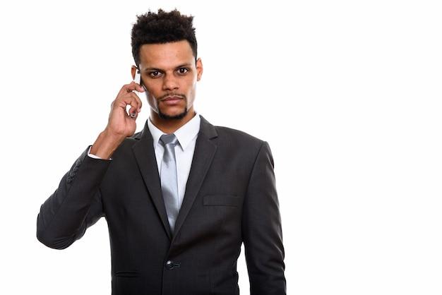 Jonge afrikaanse zakenman die op mobiele telefoon spreekt die op wit wordt geïsoleerd