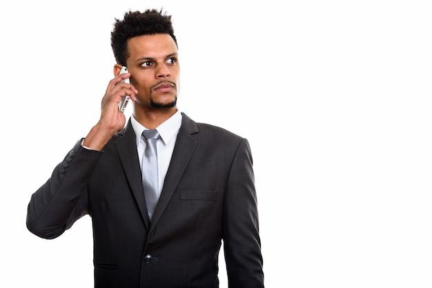 Jonge afrikaanse zakenman die op mobiele telefoon spreekt terwijl geïsoleerd op wit denkt