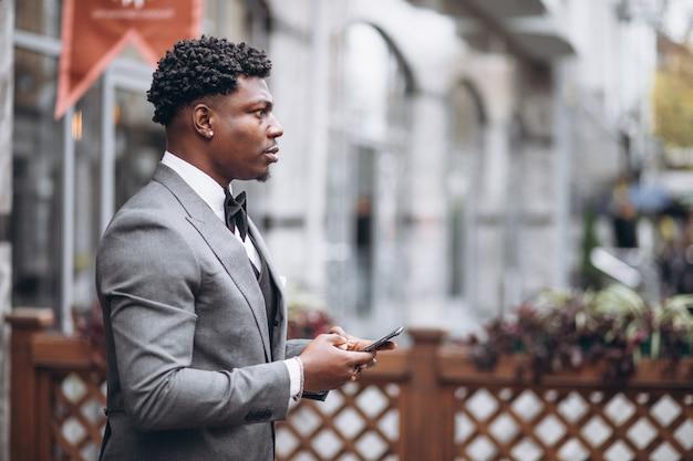 Jonge afrikaanse zakenman die telefoon met behulp van