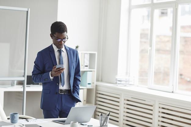 Jonge afrikaanse zakenman een bericht typen op de mobiele telefoon die zich in de buurt van zijn werkplek op moderne kantoor bevindt
