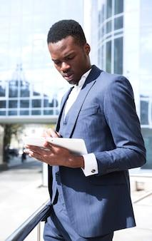 Jonge afrikaanse zakenman in blauw pak met behulp van digitale tablet in openlucht