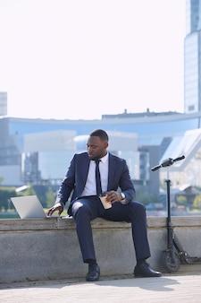 Jonge afrikaanse zakenman met laptop en koffie die presentatie voorbereidt terwijl hij aan de rivier zit tegen wolkenkrabbers en moderne gebouwen