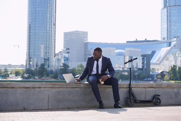 Jonge afrikaanse zakenman met laptop en koffienetwerk aan de rivier met elektrische scooter in de buurt terwijl hij tegen het stadsbeeld zit