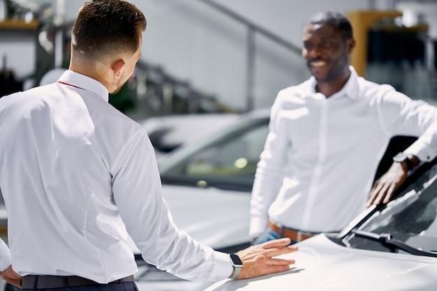Jonge afrikaanse zakenman stellen vragen over auto gepresenteerd in dealer