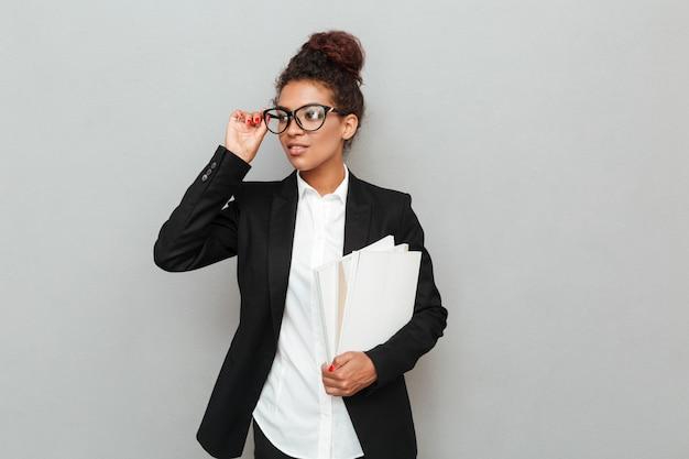 Jonge afrikaanse zakenvrouw permanent over grijze muur