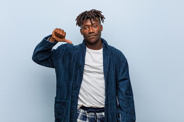 Jonge afrikaanse zwarte man met pyjama met een afkeer gebaar, duimen naar beneden. meningsverschil concept.