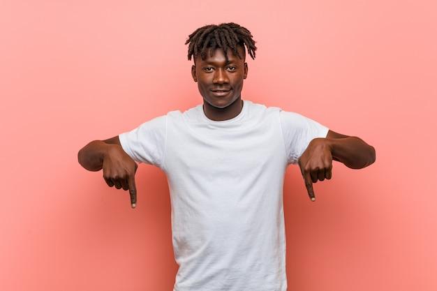 Jonge afrikaanse zwarte man wijst naar beneden met vingers, positief gevoel.