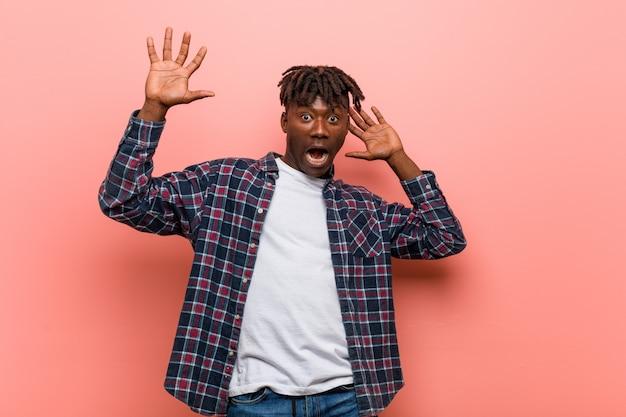 Jonge afrikaanse zwarte man wordt geschokt vanwege een dreigend gevaar