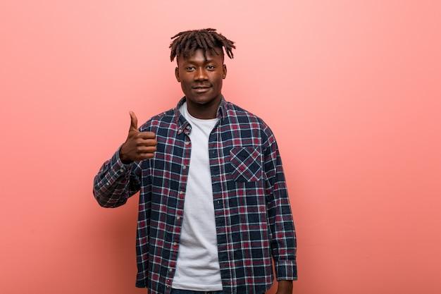 Jonge afrikaanse zwarte mens die en duim glimlacht opheft