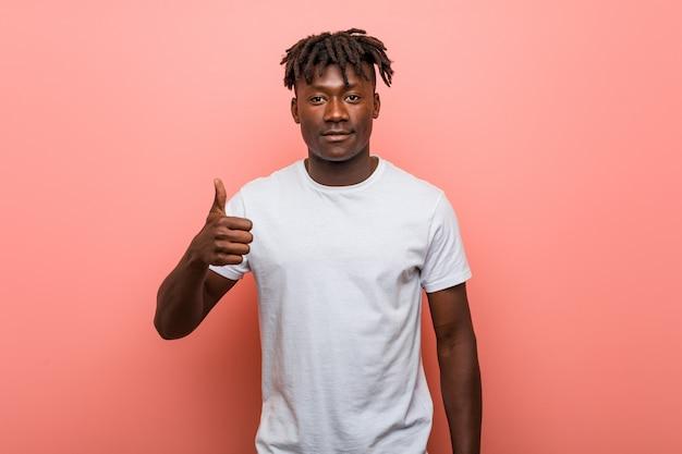 Jonge afrikaanse zwarte mens die en duim omhoog glimlacht opheft