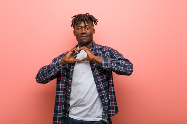 Jonge afrikaanse zwarte mens die en een hartvorm met hem handen glimlacht toont.