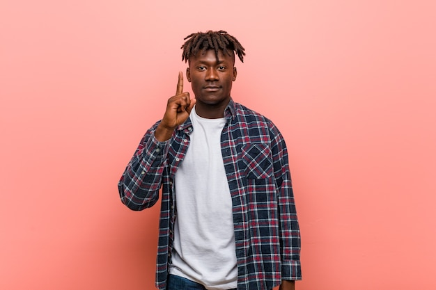 Jonge afrikaanse zwarte mens die nummer één met vinger toont.