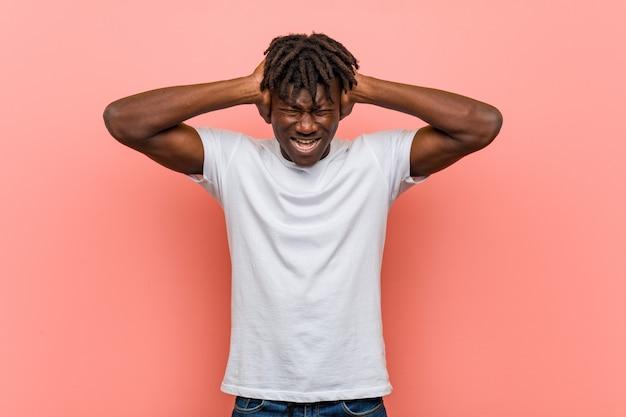 Jonge afrikaanse zwarte mens die oren behandelen met handen die niet horen te hard geluid proberen.