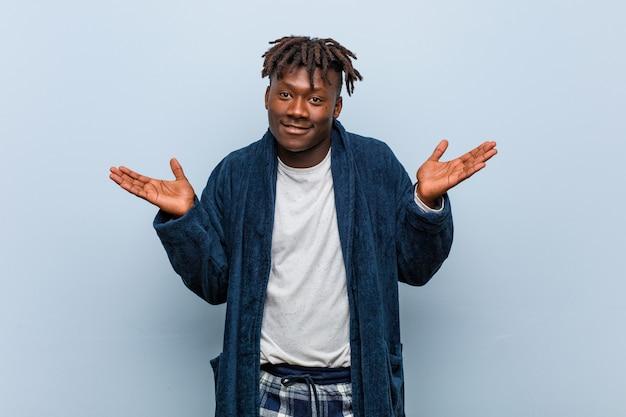 Jonge afrikaanse zwarte mens die pyjama draagt die en hem schouders ophaalt in gebaar vragen.
