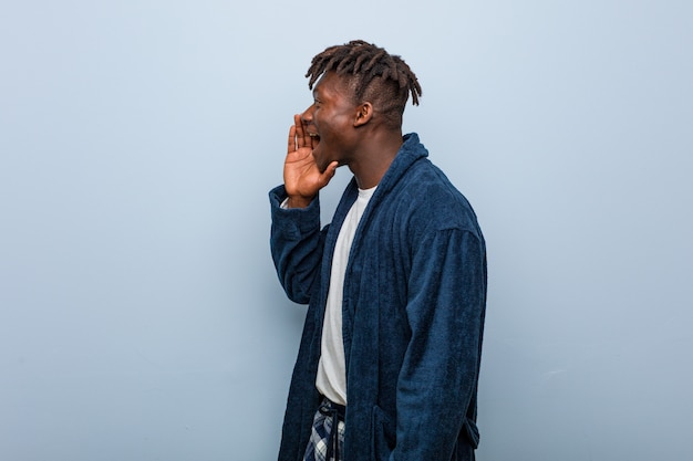 Jonge afrikaanse zwarte mens die pyjama draagt die en palm schreeuwt dichtbij geopende mond houdt.