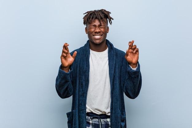 Jonge afrikaanse zwarte mens die pyjama draagt die vingers kruist voor het hebben van geluk