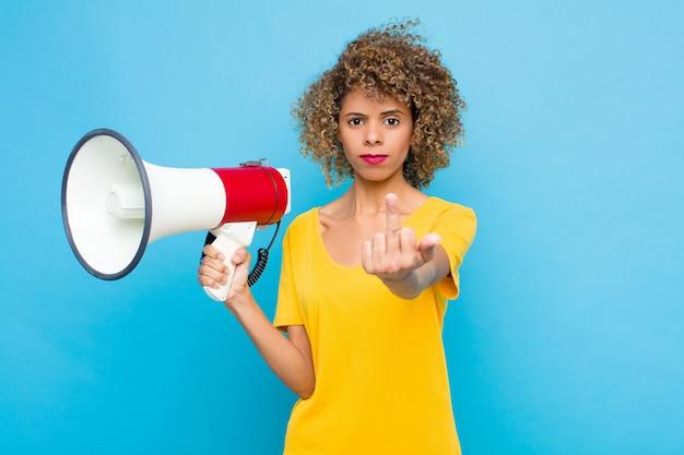 Jonge afro-amerikaan voelt zich boos, geïrriteerd, rebels en agressief, draait de middelvinger om en vecht terug met een megafoon